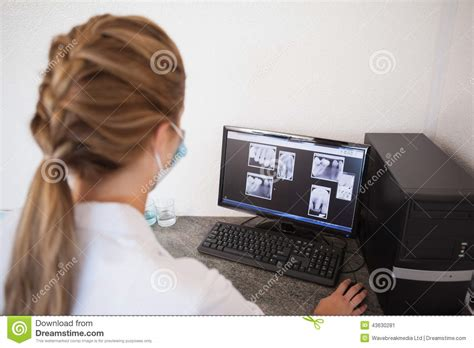 dental assistant looking at x rays on computer stock photo