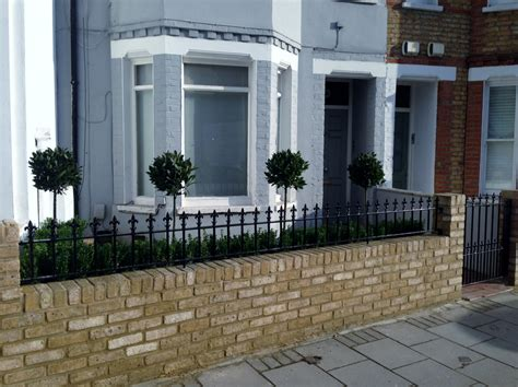 yellow brick garden wall metal rail  gate bay  buxus