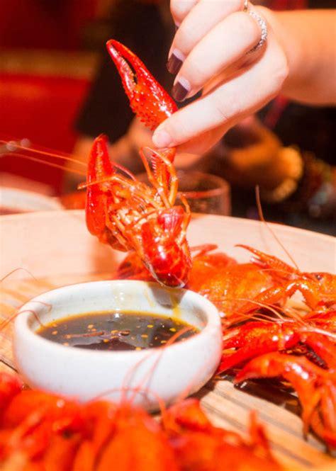 diner enjoys  popular dish  crayfish  spicy sauce