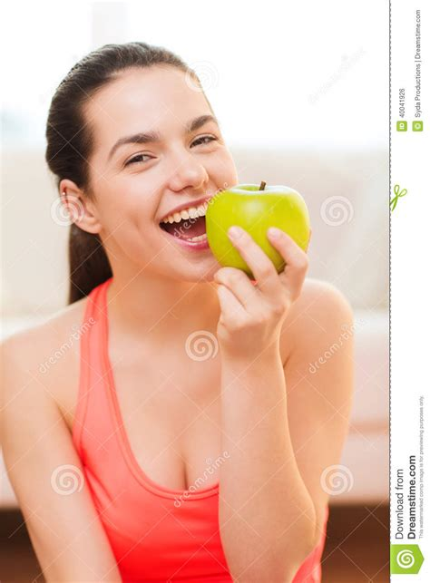 smiling with green apple at home stock photo