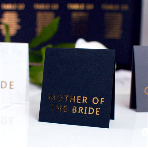 who makes the black card black and gold wedding place cards by made with