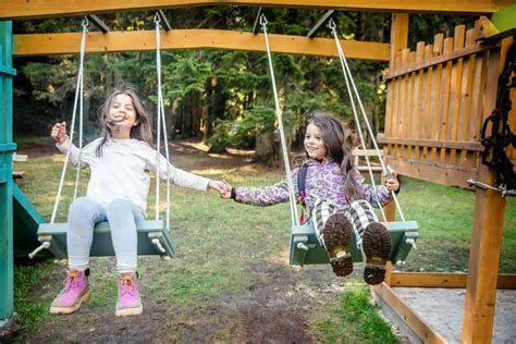 swing girls download two happy little girls swinging on the swing stock photo