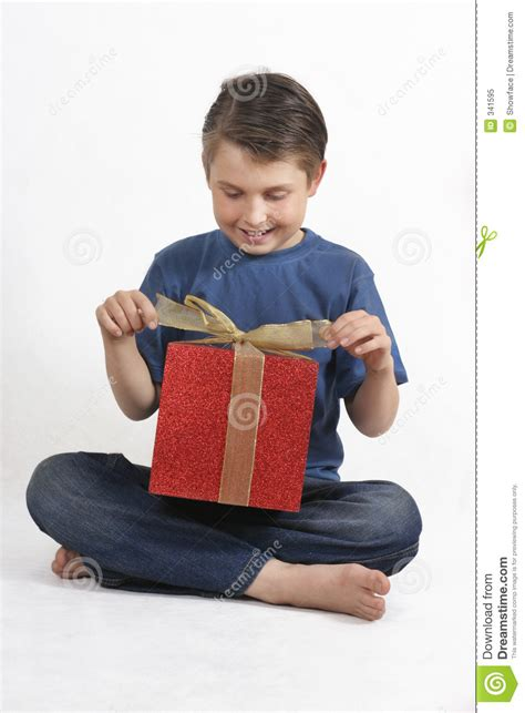 sitting child opening a present stock image image 341595