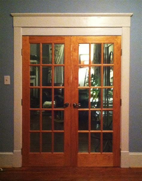glass door with brown wooden frame and bars placed
