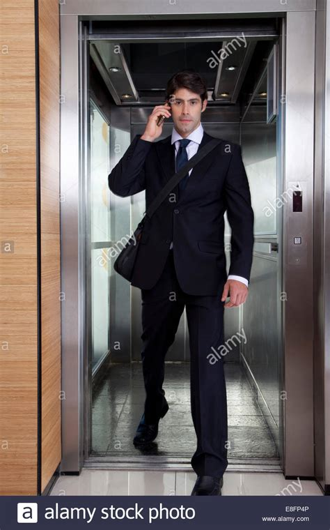 Stepping Out Of The Office But I Will Return by Businessman On Phone Stepping Out Of Office Elevator Stock