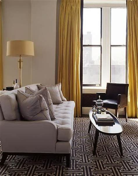 drapes on walls fted sofa black white carpet rug gold yellow curtain