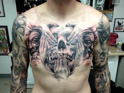 chest skull hand tattoo by carl grace