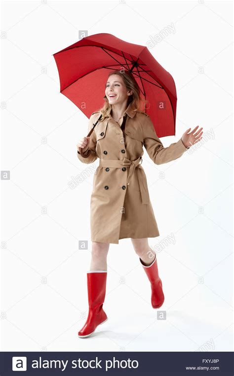 10 songs to listen to when walking the streets of paris project woman in trench coat and red rain boots holding a red
