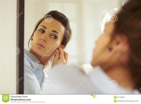 how can a woman get attractive woman putting on her earrings stock image