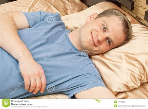bed man man lying in bed and smiling stock photo image 18079200