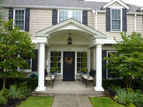 home columns black door black shutters white trim creamy tan brown brick color white garage door black