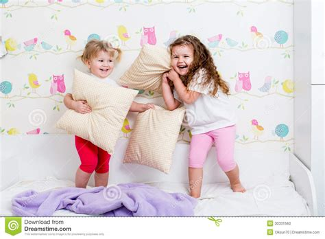 play in the bedroom children sisters play on the bed indoors stock photo