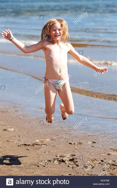 little girl models beach beautiful little girl jumping on the beach stock photo