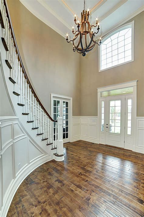 foyer house curved staircase in two story foyer with white wainscoting