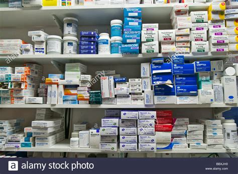 boxes of drugs piled on a pharmacists shelf stock photo