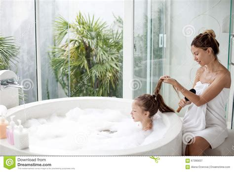 mom in bathroom mother with a child washing in bath stock image image