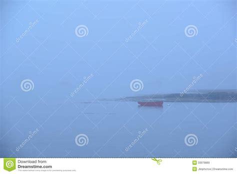 crescent roeiboot een eenzame rode roeiboot of een skiff in zware mist stock