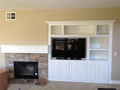 fireplace beside white built in wall entertainment center