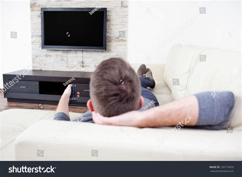 watch tv couch single man on the couch watching tv changing channels