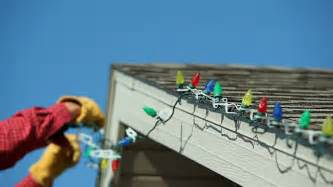 man installing led christmas lights onto a house roof