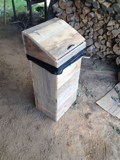 Wooden garbage can made from rough cut pine. Has removable