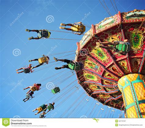 swing around fun time ride at fair spinning around with people having fun stock