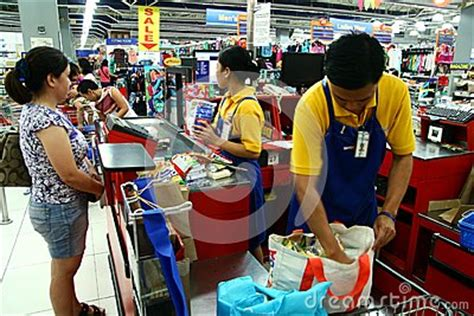 cashiers and bagger boys in a grocery store in the philippines editorial photography image