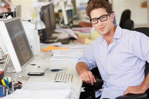 working at desk in busy creative office stock photo