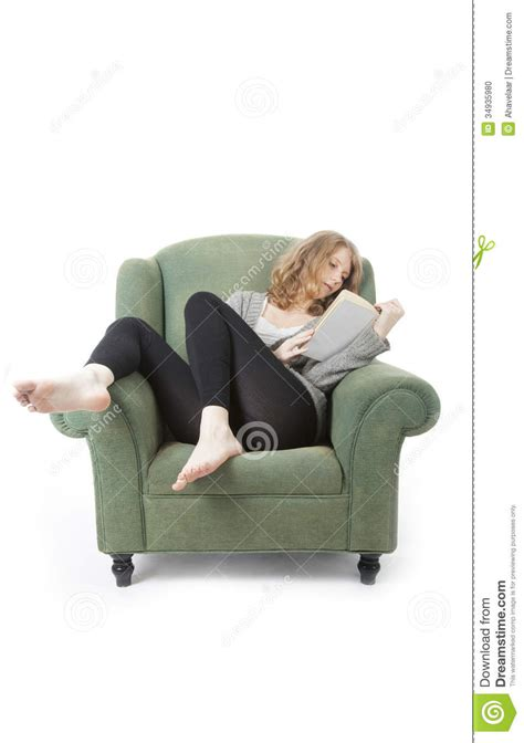 reading armchair young pretty woman reading a book in armchair stock photo