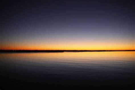 silhouette  calm sea  blue  orange clear sky