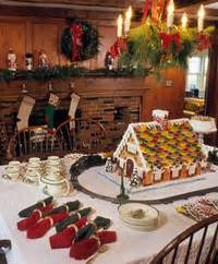 Christmas themed dessert buffet table with ginerbread house and fresh
