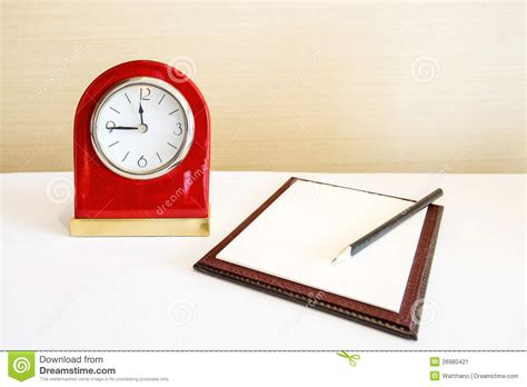 Hybrid Alarm Clock Concept by Alarm Clock And Notebook With Pencil Concept Stock Image