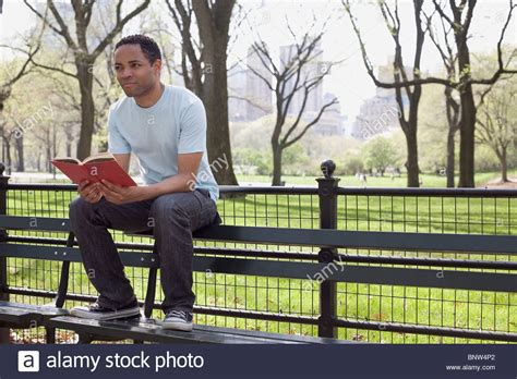 bench reading man sitting on bench reading book in central park stock photo royalty free image