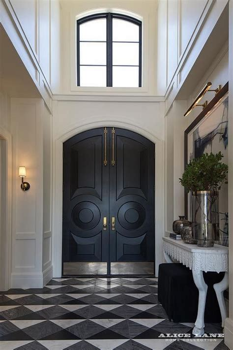 front door stories a two story foyer features black arched front doors
