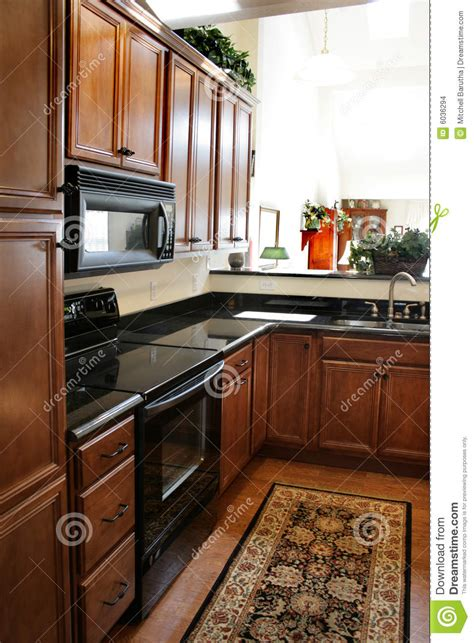 kitchen wood cabinets black  stainless stove stock