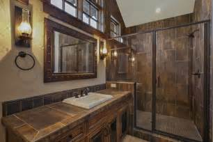 The adjoining bathroom in bronzy tile and accents the wall sconces