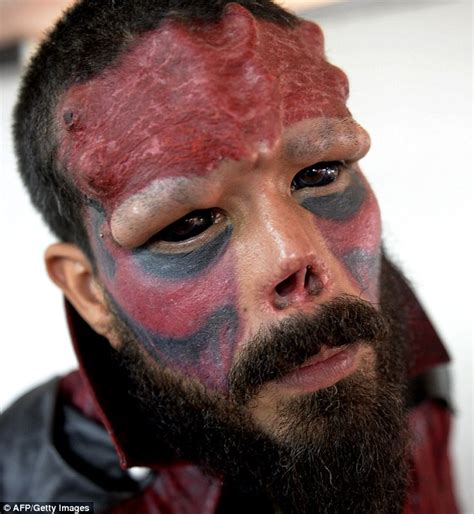 red skull man cuts off nose and severely modifies face to