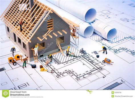 building a house online building house on blueprints with worker stock photo