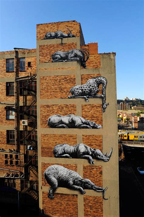 building painting roa stacks african animals on a building facade in