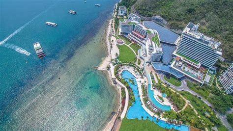 sanya marriott hotel dadonghai bay is nestled between the bay and the mountains of luhuitou park