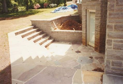 basement entrance steps leading to a small slat patio