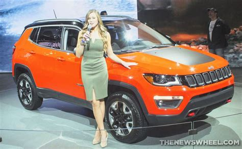 jeep car models model posing beside jeep compass at auto show the