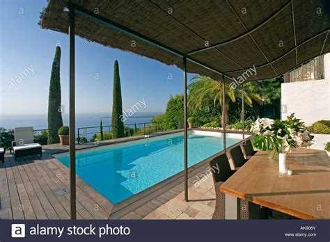 bamboo awning above table chairs on patio beside
