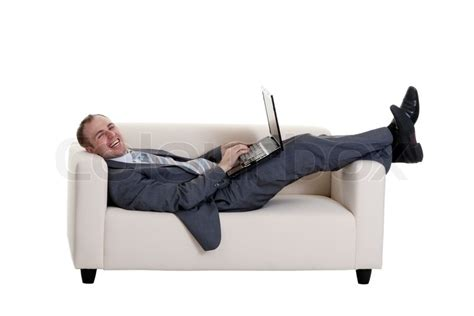 lie on couch businessman lying on the couch with a laptop on a white