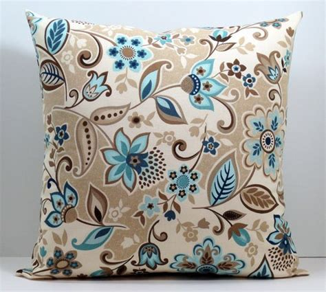 brown couch blue pillows beige blue brown and cream lacey floral decorative throw