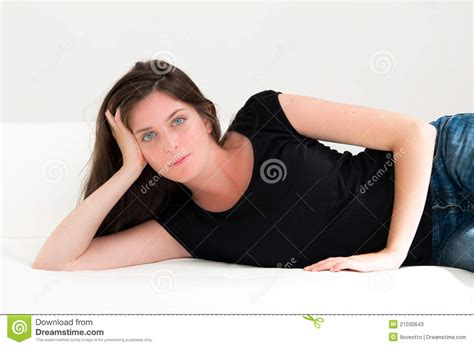 facial couch young woman holding her face on the couch stock photos