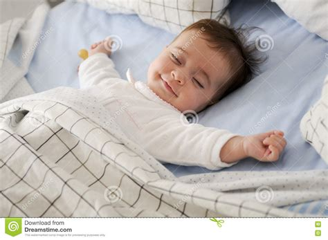 best sheets to sleep on sheets to sleep on smiling baby girl lying on a bed sleeping stock photo