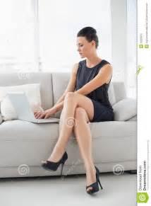 Dressed woman using laptop on sofa stock photography image 35025072