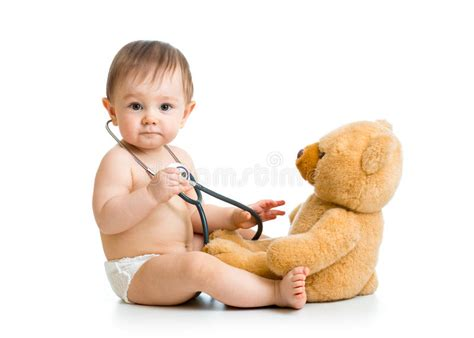 a small child in a nappy plays with the lock to a beach hut on the cute baby boy weared diaper with stethoscope and toy stock