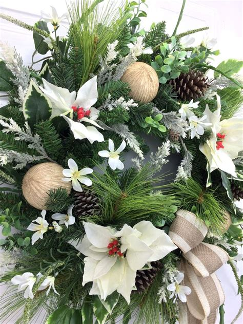 white christmas wreath with white poinsettias on an